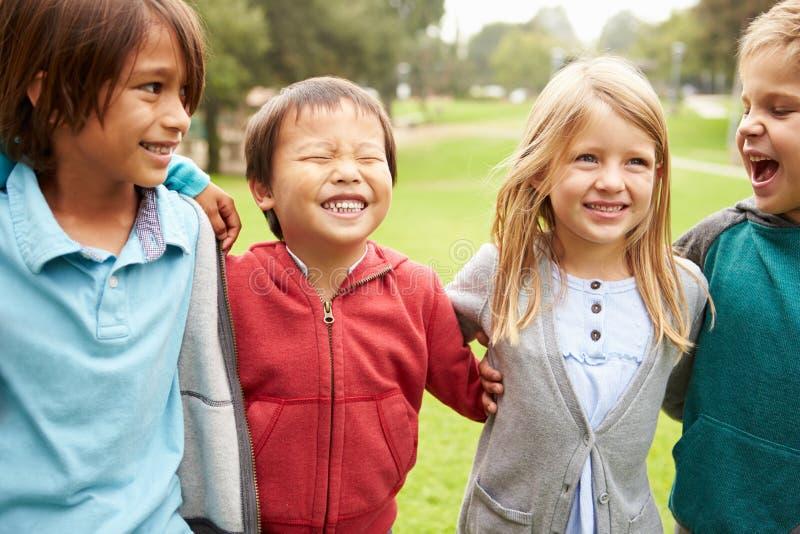 Grupo de niños jovenes que cuelgan hacia fuera en parque foto de archivo