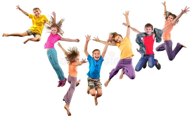 Grupo de niños juguetones alegres felices que saltan y que bailan fotos de archivo