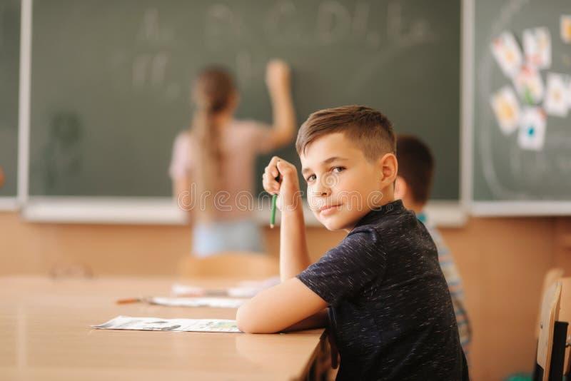 Grupo de niños de la escuela con las plumas y de cuadernos que escriben la prueba en sala de clase educación, escuela primaria, a imagen de archivo libre de regalías