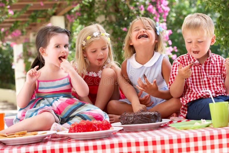Grupo de niños que comen la torta en el partido de té al aire libre fotos de archivo libres de regalías