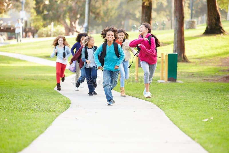 Grupo de niños que corren a lo largo de la trayectoria hacia cámara en parque imagen de archivo libre de regalías