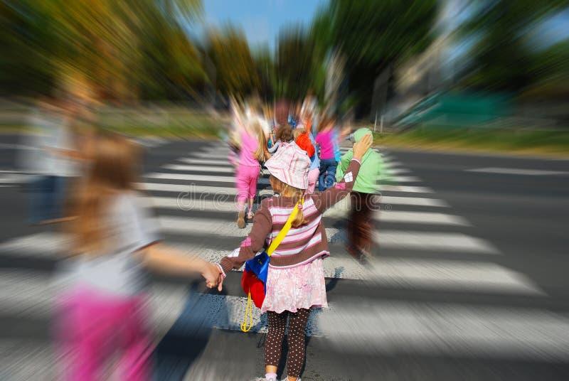 Grupo de niños que cruzan la calle fotos de archivo