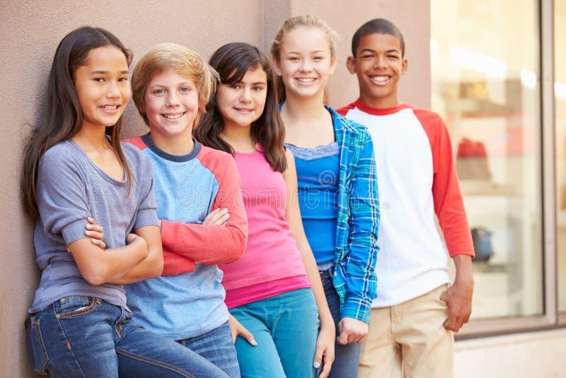 Grupo de niños que cuelgan hacia fuera junto en alameda fotografía de archivo