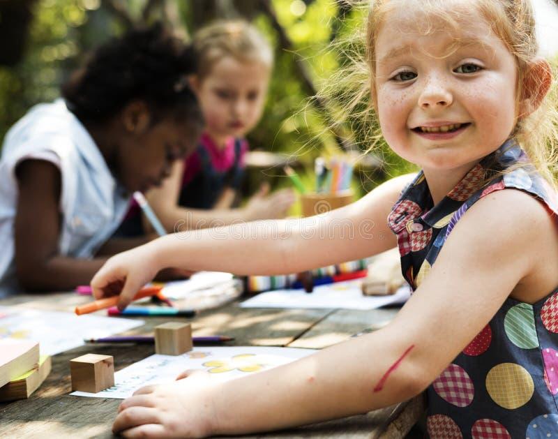 Grupo de niños que dibujan la imaginación al aire libre imagen de archivo libre de regalías