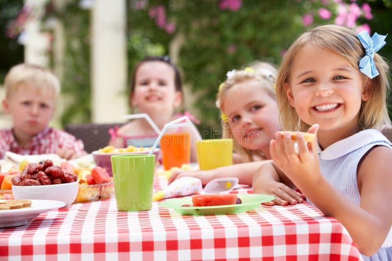 Grupo de niños que disfrutan del partido de té al aire libre fotos de archivo libres de regalías