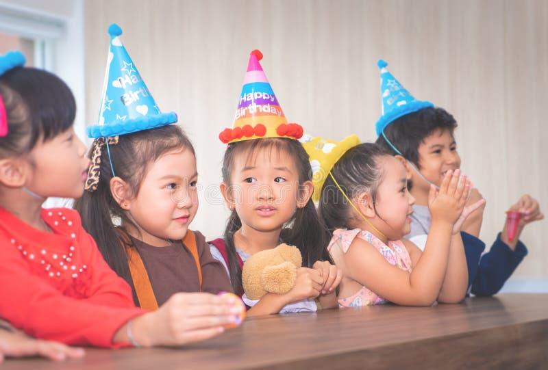 Grupo de niños que esperan para soplar la torta de cumpleaños imagen de archivo