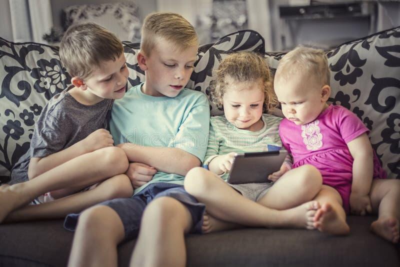 Grupo de niños que juegan con los dispositivos electrónicos de una tableta imagenes de archivo