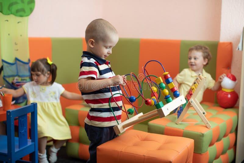 Grupo de niños que juegan en centro de la guardería o de guardería fotografía de archivo