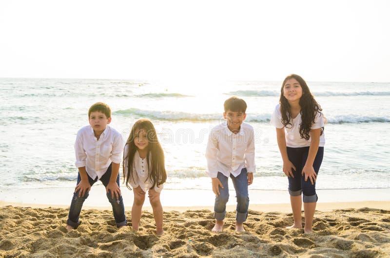 Grupo de niños que juegan en el borde del mar foto de archivo libre de regalías