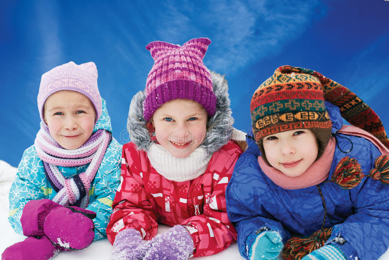 Grupo de niños que juegan en nieve en invierno foto de archivo