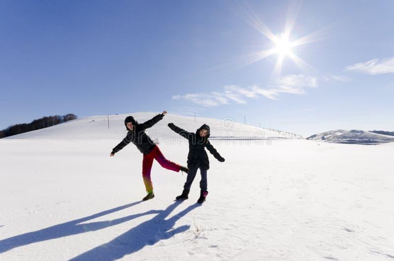 Grupo de niños que juegan en nieve en invierno en un día hermoso imagenes de archivo