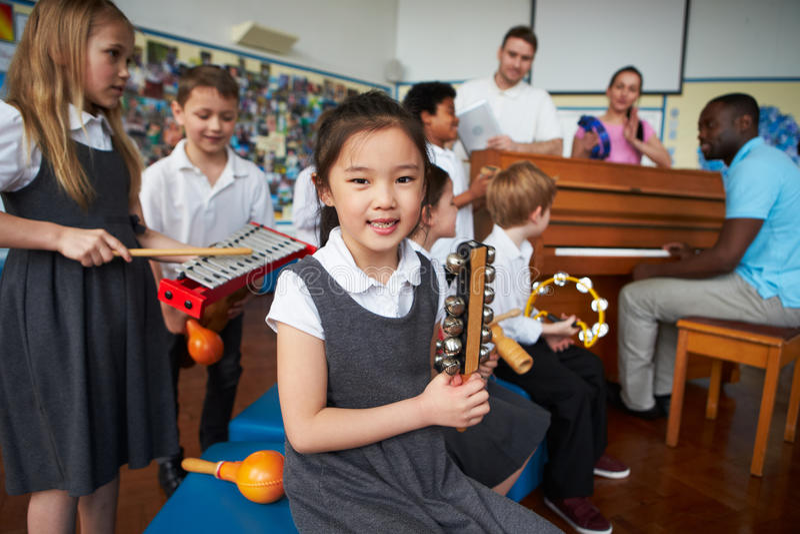 Grupo de niños que juegan en orquesta de la escuela junto fotografía de archivo