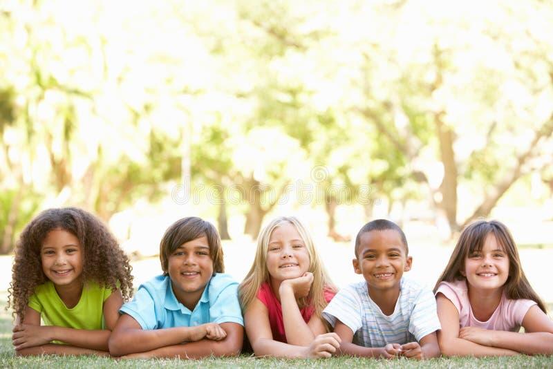 Grupo de niños que mienten en los estómagos en parque fotografía de archivo libre de regalías