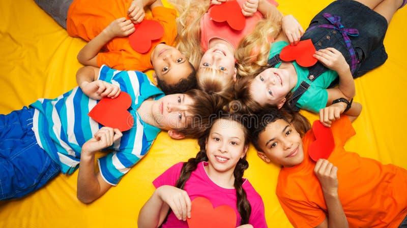 Grupo de niños que ponen con los corazones rojos fotografía de archivo libre de regalías