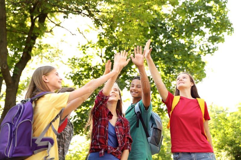 Grupo de niños que ponen las manos juntas al aire libre fotografía de archivo