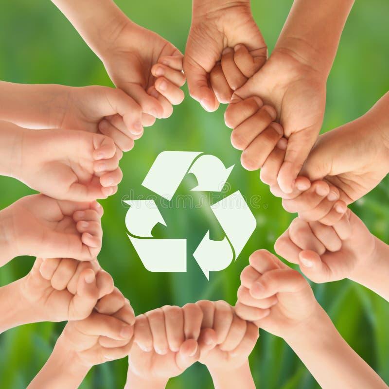 Grupo de niños que ponen las manos juntas y que reciclan símbolo contra fondo borroso ilustración del vector