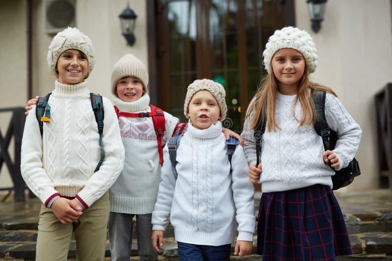 Grupo de niños que presentan por la puerta de la escuela imagenes de archivo