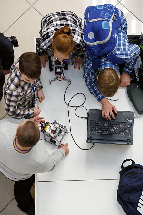 Grupo de niños que programan el robot en las competencias de la robótica imagen de archivo