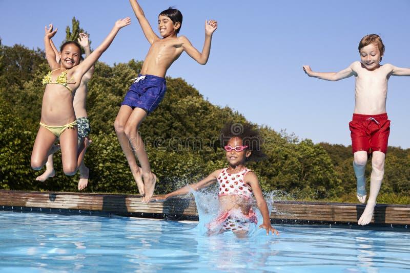 Grupo de niños que saltan en piscina al aire libre fotos de archivo