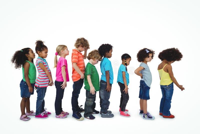 Grupo de niños que se colocan en una línea fotografía de archivo libre de regalías