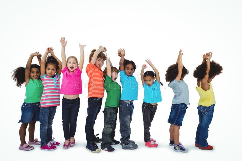 Grupo de niños que se colocan en una línea con los brazos aumentados fotografía de archivo libre de regalías