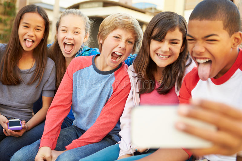 Grupo de niños que se sientan en banco en la alameda que toma Selfie imagenes de archivo