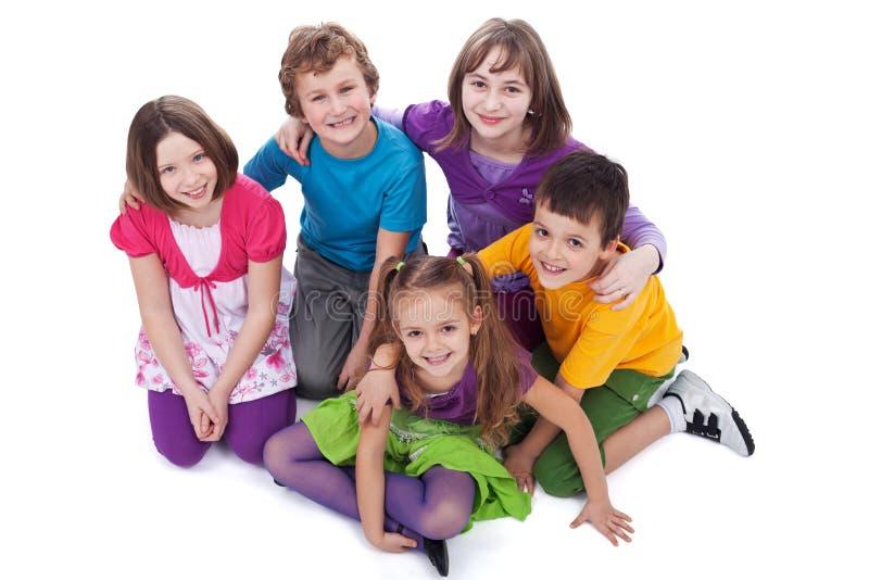 Grupo de niños que se sientan en el piso fotos de archivo
