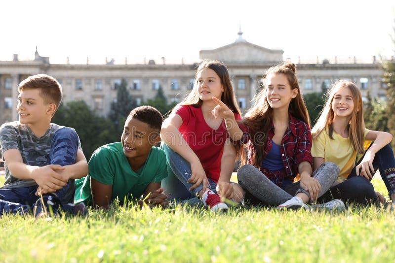 Grupo de niños que se sientan en hierba al aire libre imagen de archivo