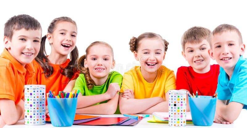 Grupo de niños que se sientan en una tabla imágenes de archivo libres de regalías