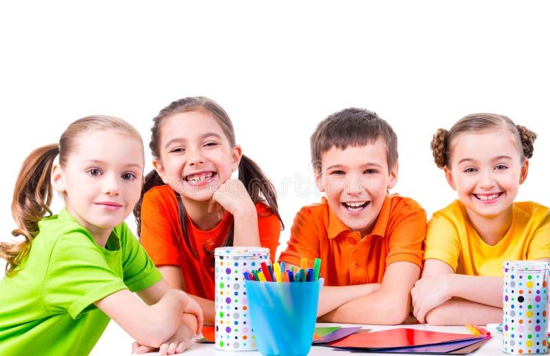 Grupo de niños que se sientan en una tabla foto de archivo