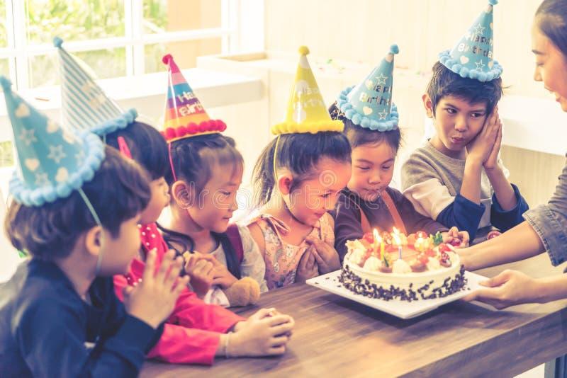 Grupo de niños que soplan el partido de la torta de cumpleaños imágenes de archivo libres de regalías
