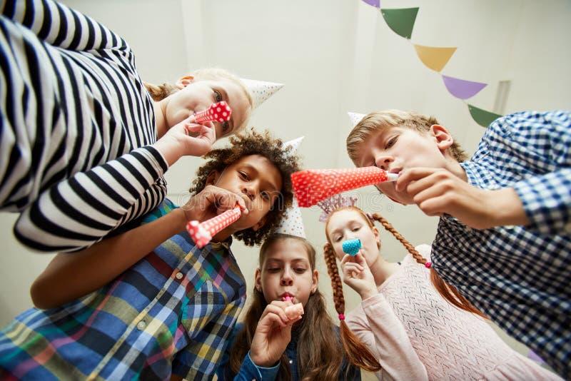 Grupo de niños que soplan los cuernos del partido fotos de archivo