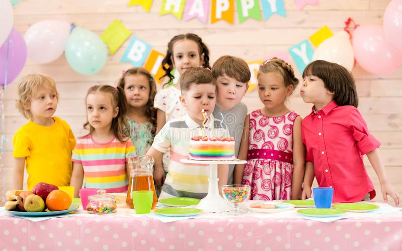 Grupo de niños que soplan velas en la torta en la fiesta de cumpleaños foto de archivo