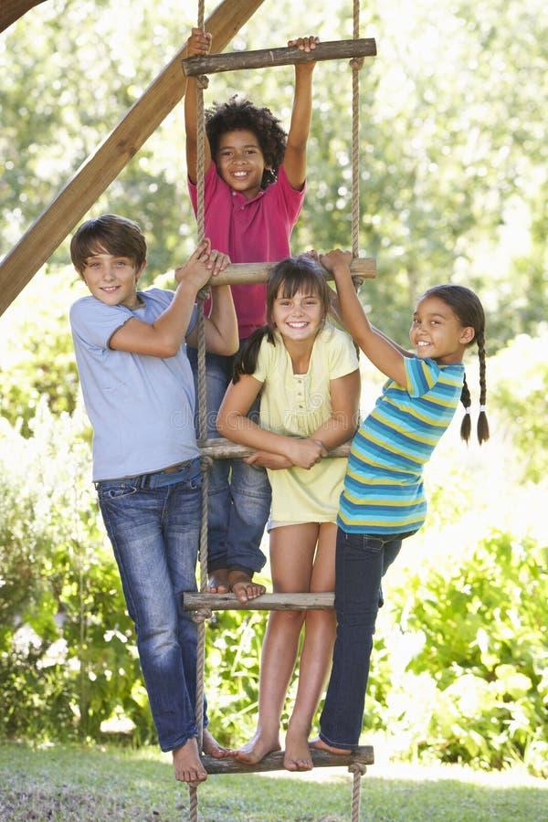 Grupo de niños que suben la escalera de cuerda a la casa del árbol imagenes de archivo