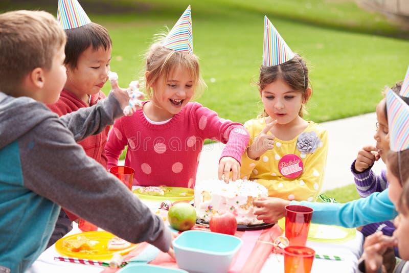 Grupo de niños que tienen fiesta de cumpleaños al aire libre fotos de archivo libres de regalías