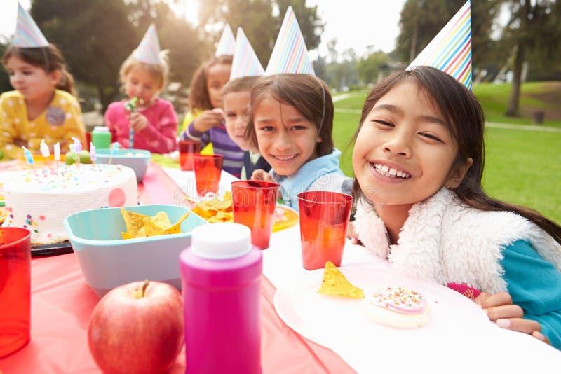 Grupo de niños que tienen fiesta de cumpleaños al aire libre fotografía de archivo libre de regalías