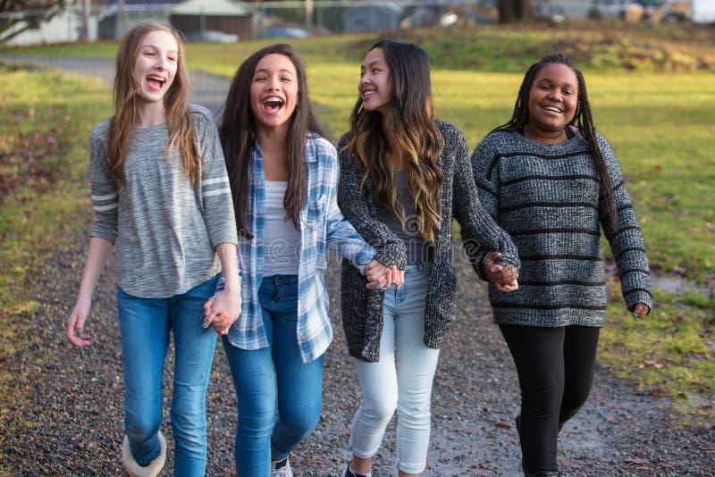 Grupo de niños sanos, felices que caminan y que llevan a cabo las manos mientras que imágenes de archivo libres de regalías