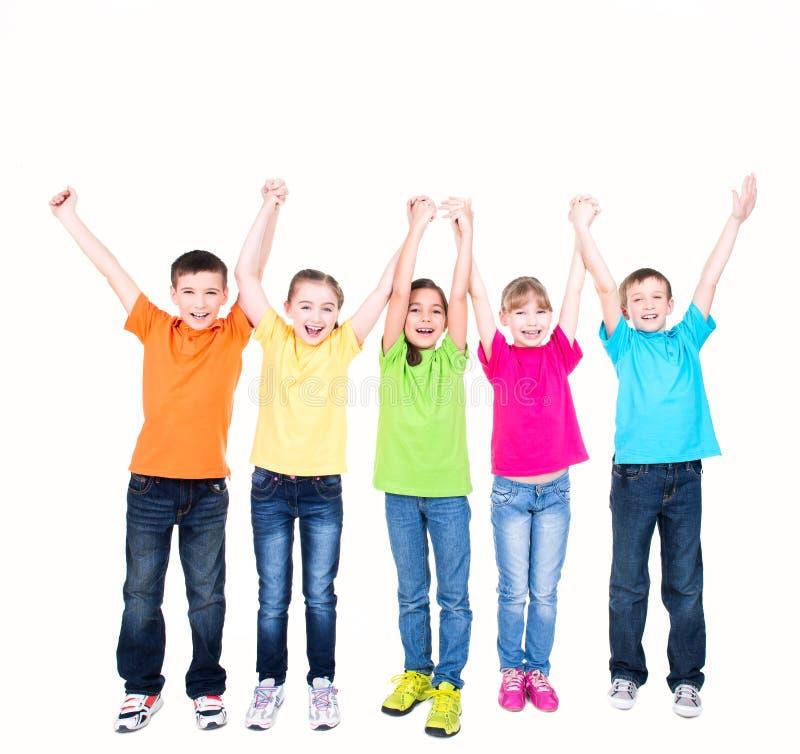 Grupo de niños sonrientes con las manos aumentadas. imagen de archivo