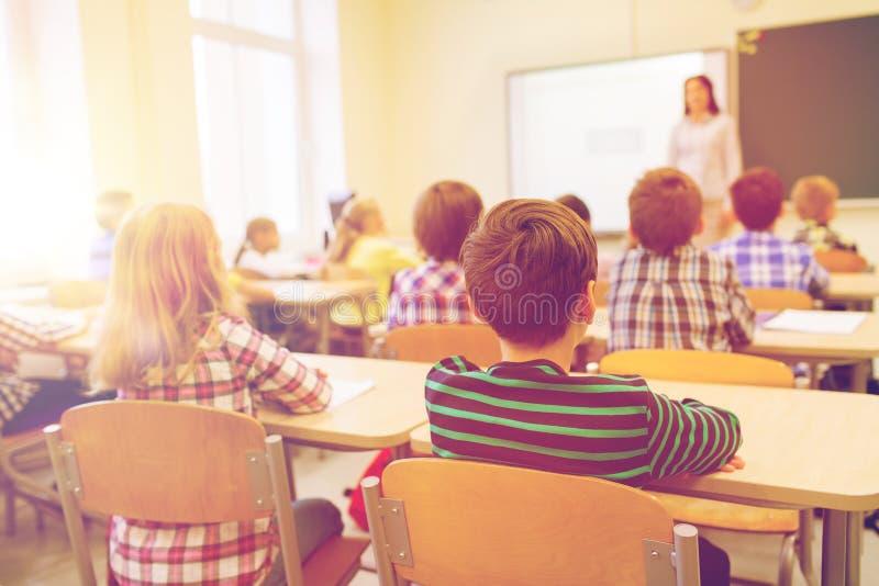 Grupo de niños y de profesor de la escuela en sala de clase foto de archivo