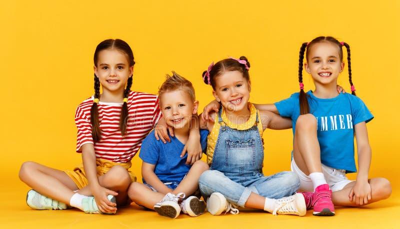 Grupo de ni?os felices alegres en fondo amarillo coloreado imágenes de archivo libres de regalías