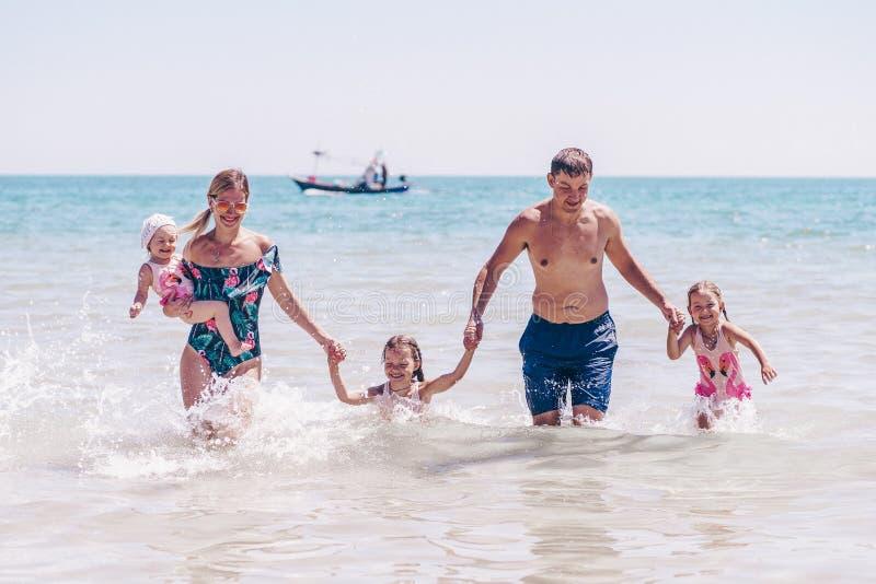Grupo de ni?os felices que juegan y que salpican en la playa del mar Ni?os que se divierten al aire libre Vacaciones de verano y  foto de archivo libre de regalías