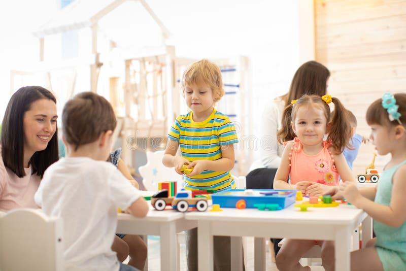 Grupo de ni?os que juegan junto en la sala de clase en guarder?a o preescolar foto de archivo libre de regalías