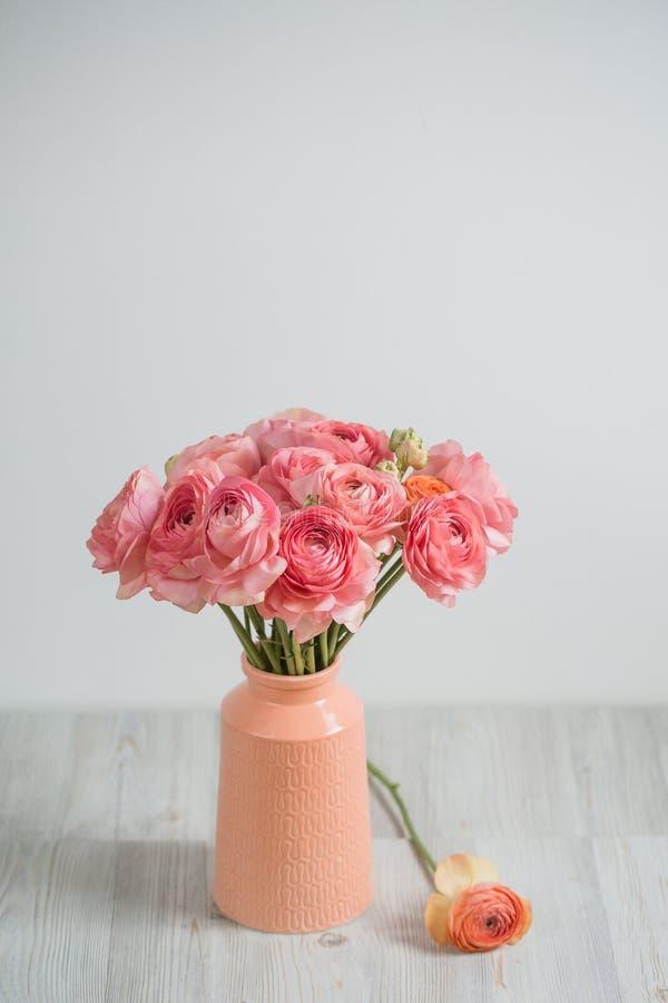 Grupo de pálido - fundo persa da luz do botão de ouro do ranúnculo cor-de-rosa, superfície de madeira Vaso de vidro foto de stock
