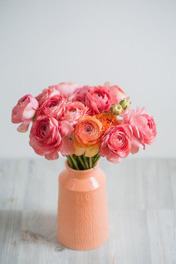 Grupo de pálido - fundo persa da luz do botão de ouro do ranúnculo cor-de-rosa, superfície de madeira Vaso de vidro foto de stock royalty free
