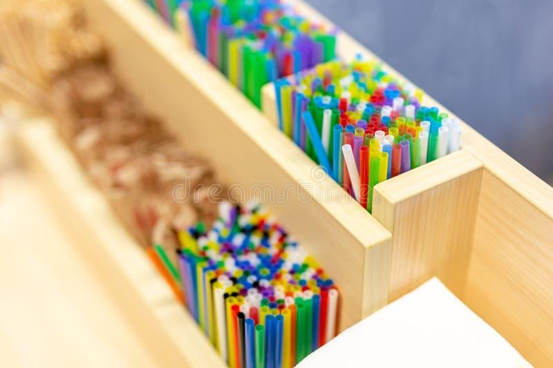 Grupo de palhas sorvendo plásticas coloridas na caixa de madeira no contador do café Decoração e acessórios das bebidas CCB color fotos de stock royalty free