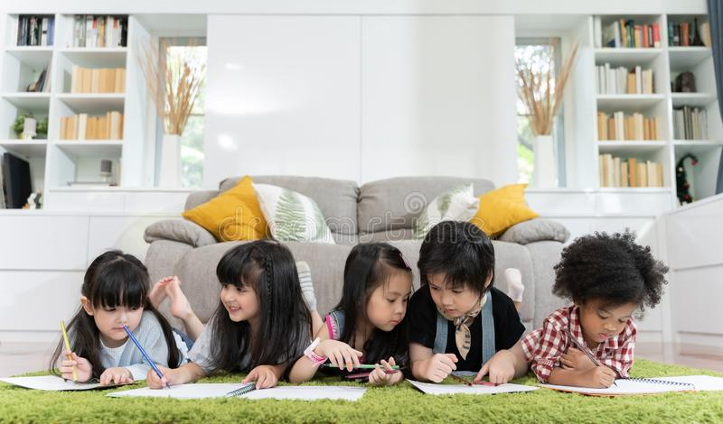Grupo de papel de tiragem pré-escolar pequeno das crianças com lápis da cor retrato do conceito da educação dos amigos das crianç imagem de stock royalty free