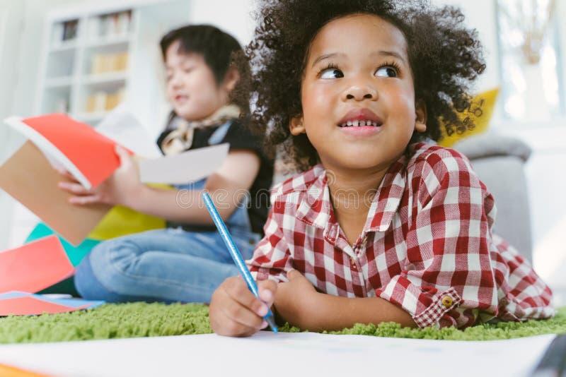 Grupo de papel de tiragem pré-escolar pequeno das crianças com lápis da cor retrato da menina africana com conceito da educação d foto de stock royalty free
