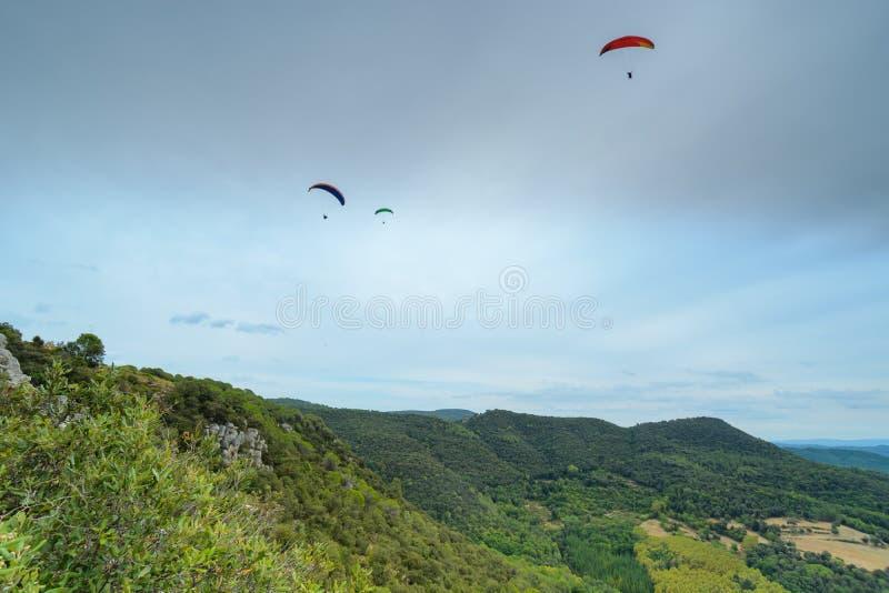 Grupo de paragliders acima das montanhas foto de stock royalty free