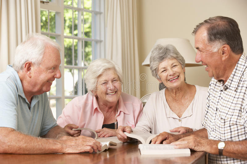 Grupo de pares mayores que asisten al libro que lee al grupo imagenes de archivo