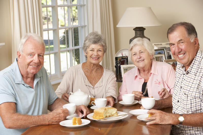 Grupo de pares mayores que goza del té de tarde junto en casa imágenes de archivo libres de regalías